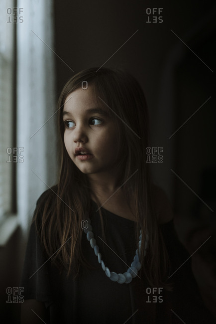Close-up of thoughtful girl looking through window while standing in darkroom at home