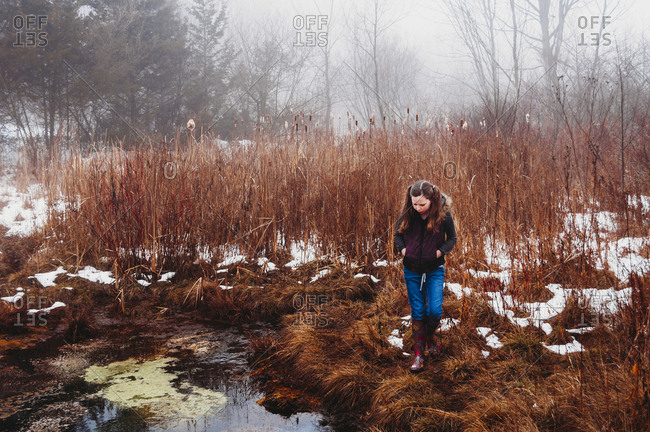 Girl walking on grassy field by lake in forest during winter