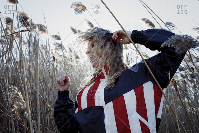 Cheerful woman wearing American Flag jacket while dancing amidst plants on field