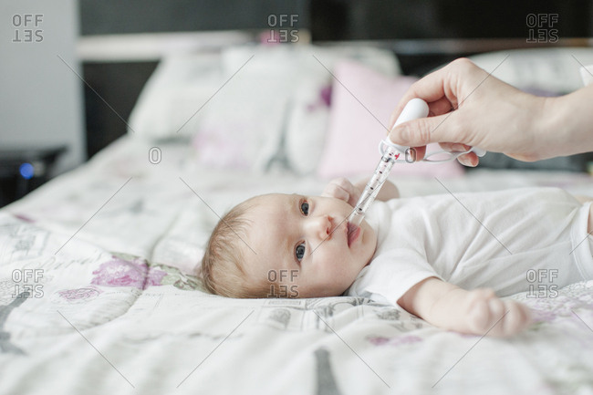 Cropped hand of mother giving daughter medicine with pipette on bed at home