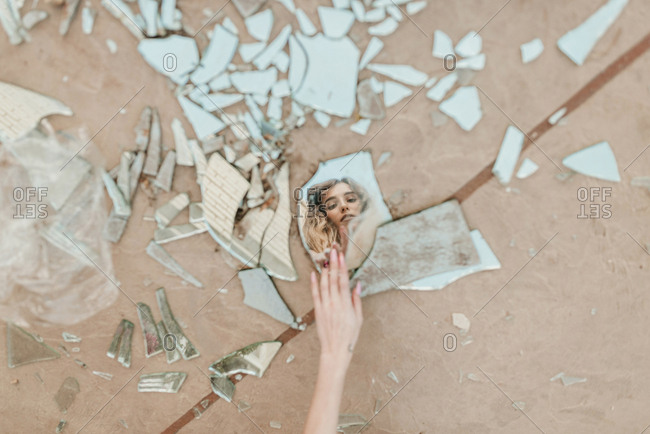 Cropped hand of woman touching broken mirror pieces on footpath