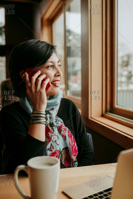 Smiling woman answering smart phone while looking through window at cafe