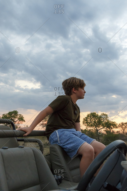 Thoughtful boy sitting on off-road vehicle against cloudy sky during sunset