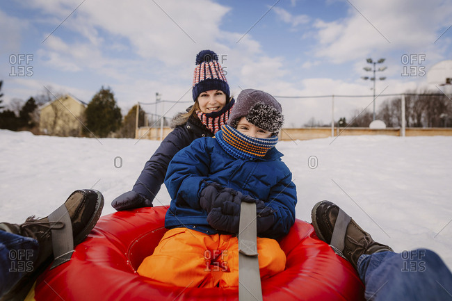 Portrait of mother and son tobogganing with tube sled on snow covered field against cloudy sky