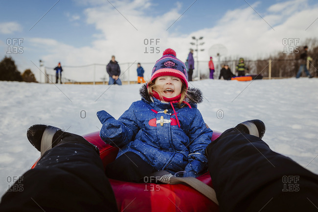 Low section of mother with daughter tobogganing on snow covered field against cloudy sky