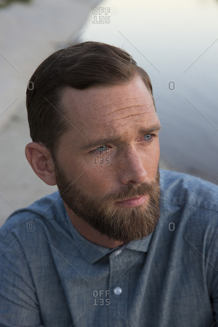 High angle close-up of thoughtful man sitting by river