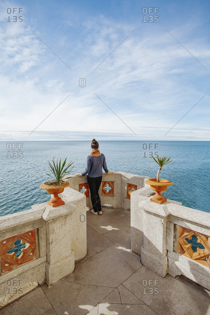 Rear view of young woman looking at sea while standing on building terrace against sky