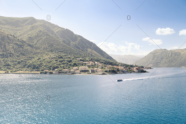 Scenic view of sea against mountains and sky during sunny day