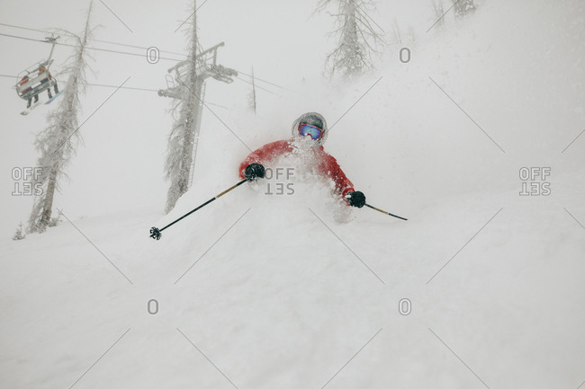 Man skiing on snow covered mountain in forest