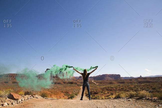 Rear view of carefree man with arms raised holding green smoke bombs while standing on dirt road against clear sky amidst desert