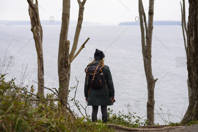 Rear view of woman with backpack standing by sea against sky at Discovery Park