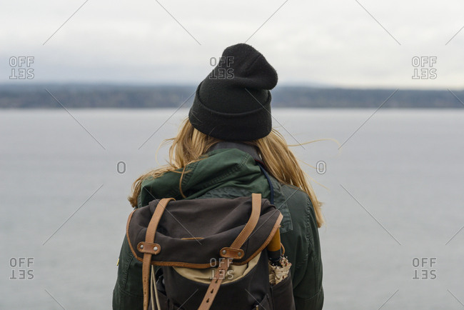 Rear view of woman with backpack standing by sea against cloudy sky at Discovery Park