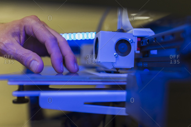 Cropped hand of engineer examining 3D printer in office