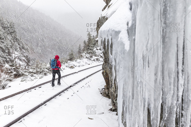 Rear view of woman walking on snow covered railroad track during snowfall at White Mountains
