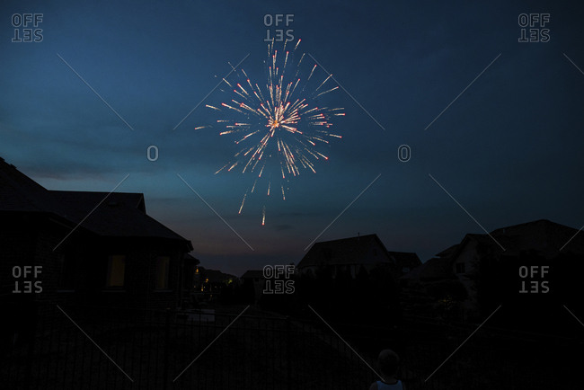 Low angle view of firework display over silhouette houses against sky at night