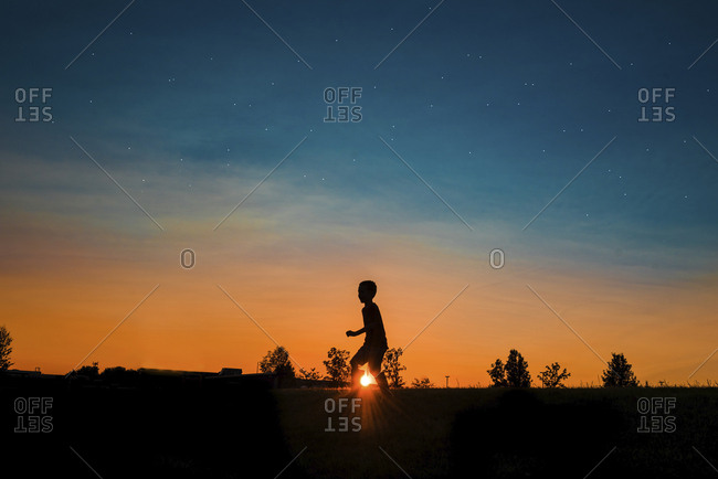 Silhouette boy walking on field against sky during sunset