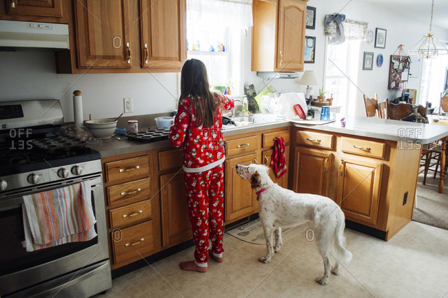 Rear view of girl preparing food while standing by dog in kitchen