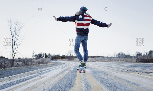 Rear view of carefree woman with arms outstretched skateboarding on road against clear sky during winter