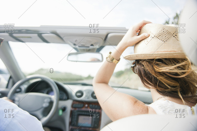Rear view of woman wearing hat while traveling in convertible against sky