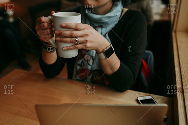 Midsection of woman wearing smart watch while holding coffee mug at cafe