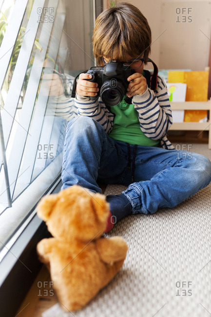 Boy photographing teddy bear while sitting at home