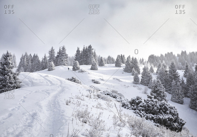 Distant view of man hiking on snow covered mountain against cloudy sky