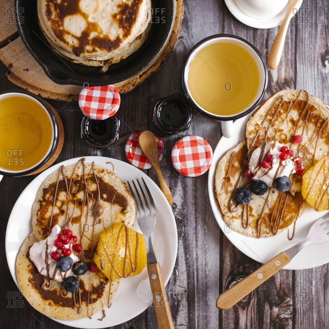 Overhead view of pancakes with preserves and fruits on wooden table
