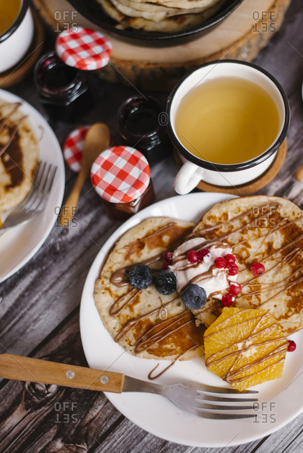 Close-up of pancakes with preserves and fruits on wooden table