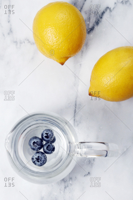 Overhead view of blueberries in jug by lemons on table