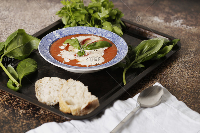 High angle view of tomato soup by bread and herbs served in tray on table