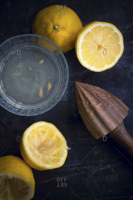 Overhead view of wooden juicer and lemon slices on table