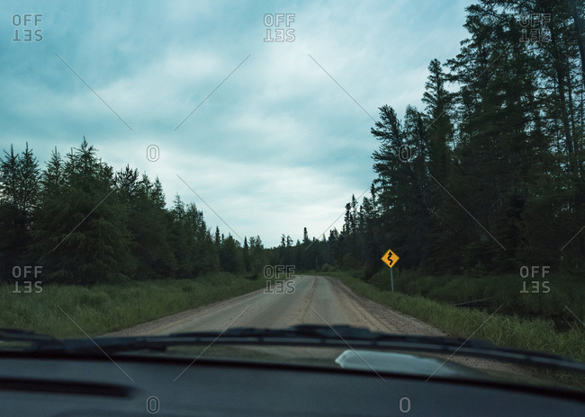 Empty road amidst trees against cloudy sky seen through windshield
