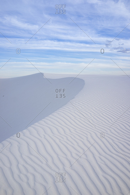 Scenic view of wave patterns on desert against cloudy sky at White Sands National Monument