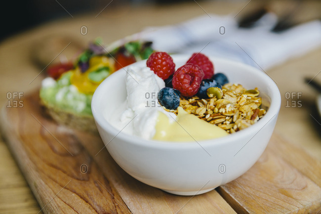 Close-up of breakfast served in bowl on wooden cutting board