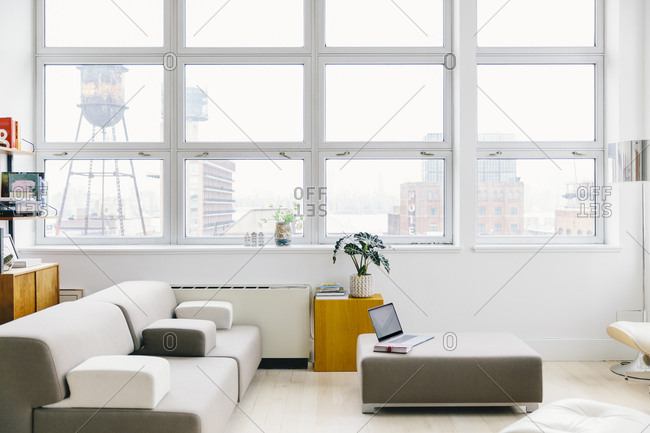 Furniture on hardwood floor against windows in modern startup office