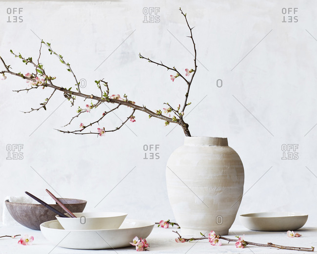 Flower vase with bowls and plates on table against wall