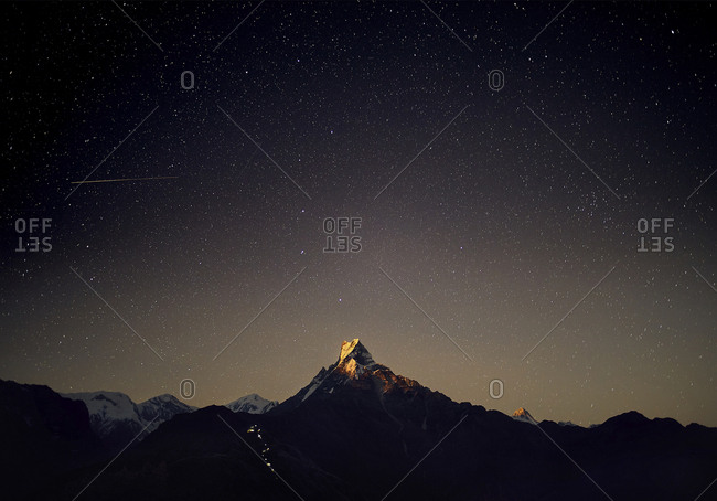 Scenic view of Machapuchare Mountains against star field at night