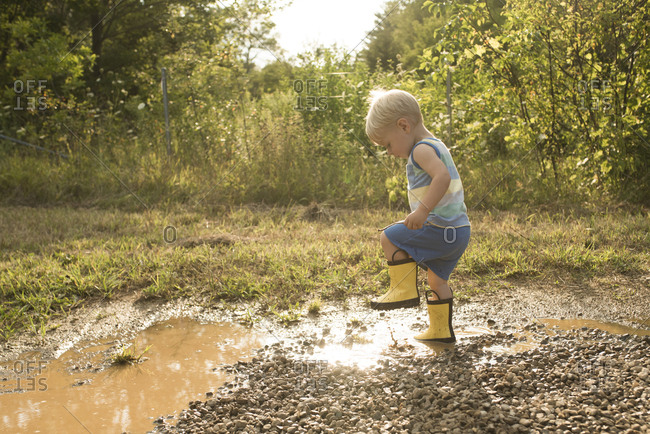 Side view of playful boy stamping foot in puddle at forest