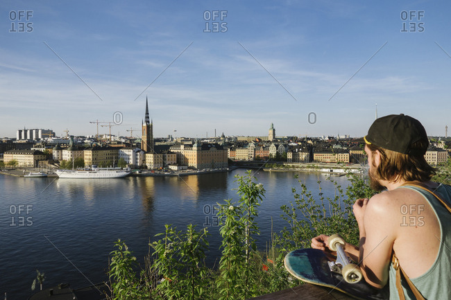 Young man with skateboard looking at city across river