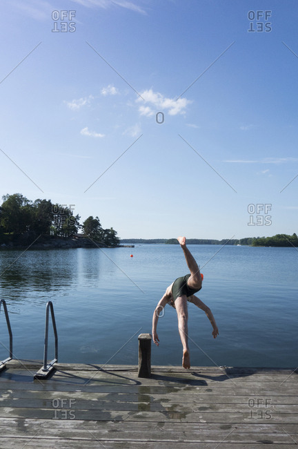 Man jumping into lake from jetty