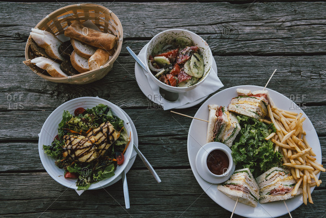 Sandwiches, salad and French fries on wooden table