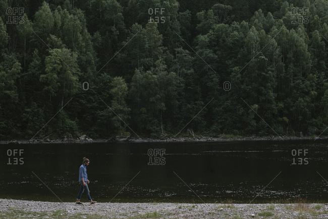 Young man walking on lakeshore