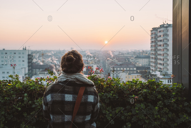 Rear view of woman looking at city at sunrise