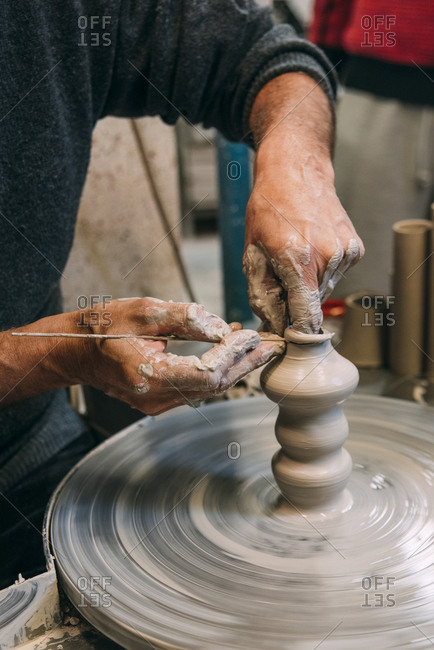Male potter's hands working on pottery wheel