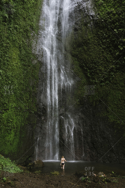 Rear view of woman in bikini walking towards waterfall
