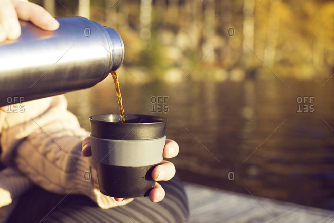 Woman pouring tea from thermos, close-up of hands