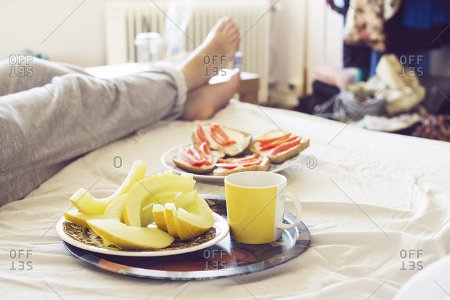 Legs of person lying on bed, snacks on plates in foreground
