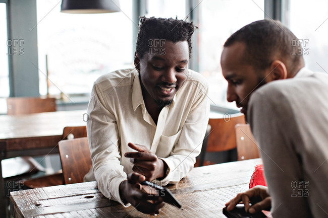 Smiling young man showing mobile phone to friend while sitting at table in restaurant