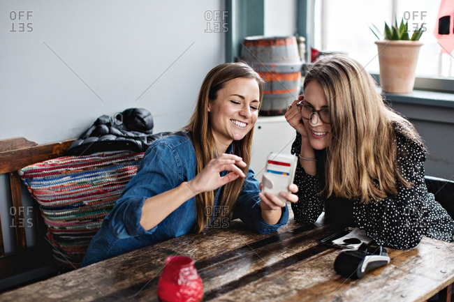 Smiling woman showing mobile phone to friend while sitting at table in restaurant