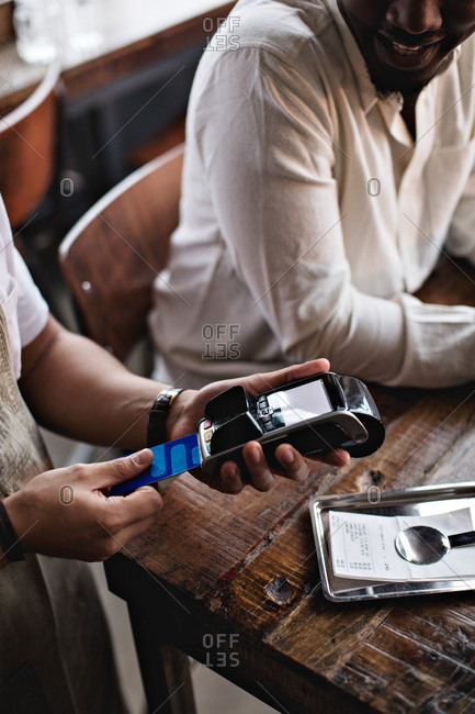 Cropped image of owner using credit card reader by customers at table in restaurant